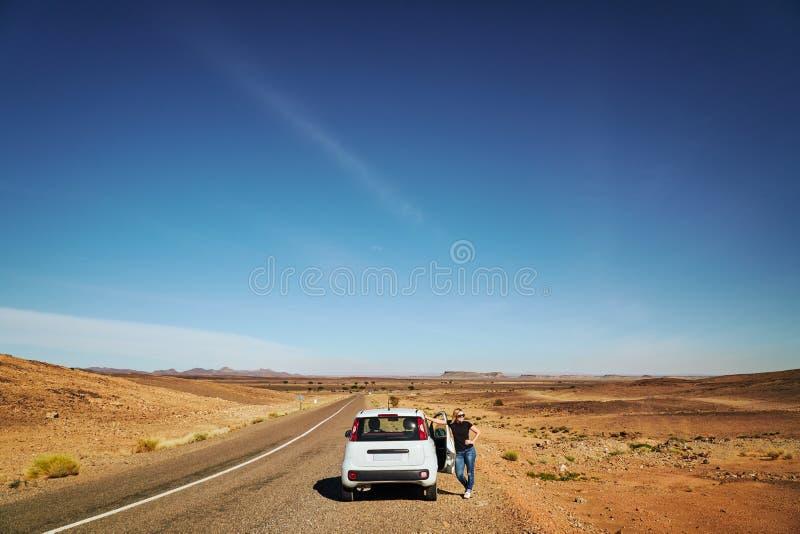 Eine blonde Mädchenstellung in der Wüste nahe bei dem defekten Auto stockfotografie