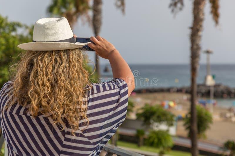 Eine blonde touristische Frau mit Hut macht Fotos mit ihrem Telefon von einem paradiasic Strand lizenzfreies stockbild