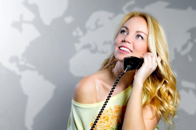 Eine Blondine mit einem Telefon stockbild