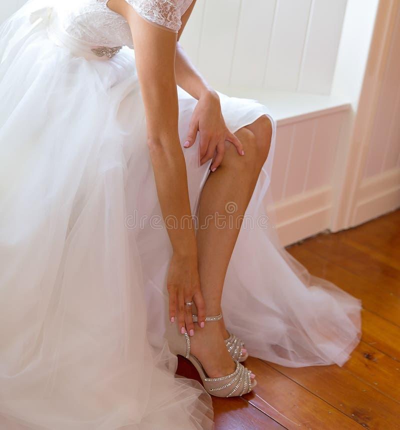 Eine Braut befestigt ihren Schuh, während sie zu ihrer Hochzeit fertig wird stockbilder