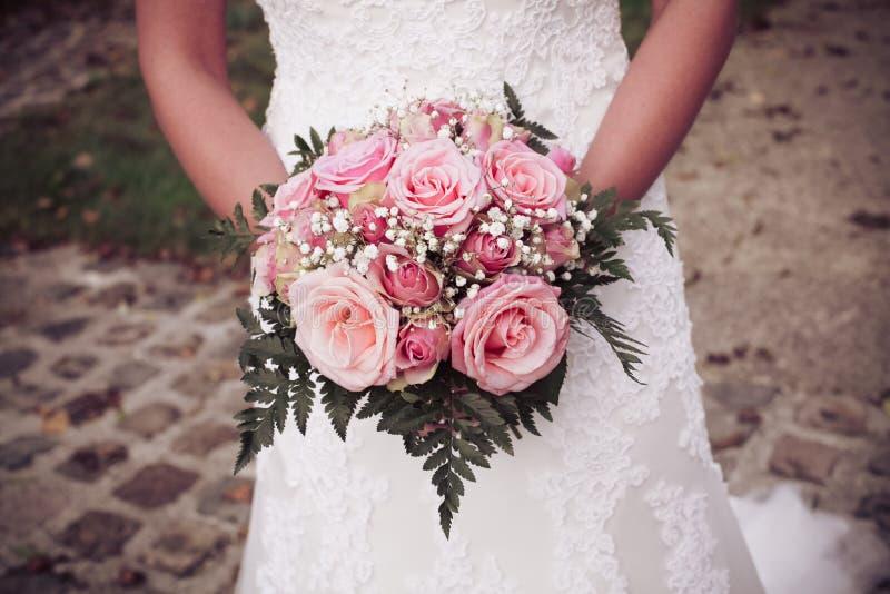 Eine Braut, die ihren Blumenstrauß von Rosen hält stockfoto