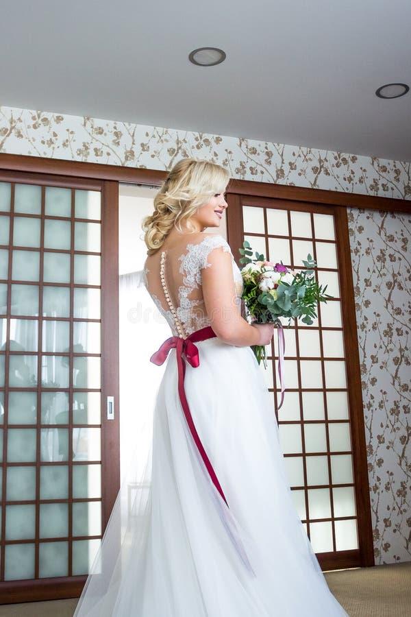 Eine Braut mit Make-up und Frisurständen in einem Hotelzimmer in einem Heiratskleid mit einem roten Band und mit einem Heiratsblu stockbild