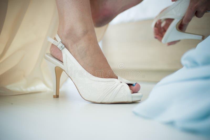 Eine Braut zu sein wird bei ihren Schuhen in Vorbereitung auf sie wir geholfen stockbild