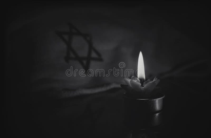 Eine brennende Kerze nahe bei dem Davidsstern lizenzfreie stockbilder