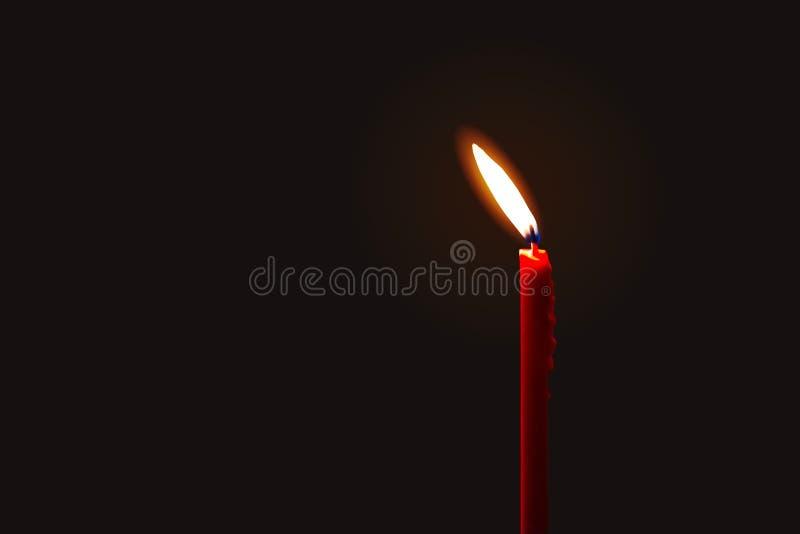 Eine brennende rote Kerze lokalisiert auf dunklem Hintergrund lizenzfreie stockfotos
