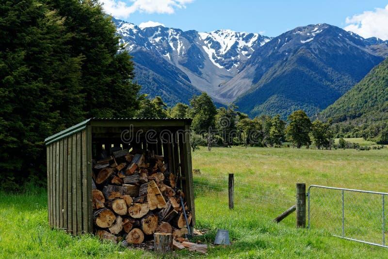 Eine Brennholzhalle, die mit Brennholz auf Lager, Schnee bedeckte Berge im Hintergrund mit einer Kappe stockfotos