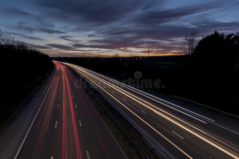 Eine BRITISCHE Autobahn, bei Sonnenuntergang, wenn die hellen Spuren durch den Verkehr hergestellt sind lizenzfreie stockbilder