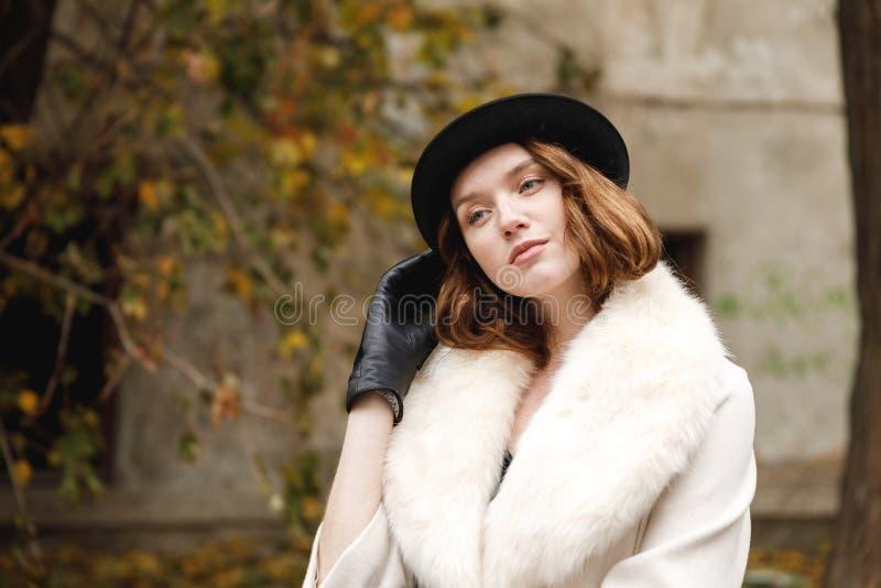 Eine Brunettedame im Hut und Handschuhe und Mantel steht, geraderichtend ihren Hut mit ihrer Hand retro draußen stockfoto