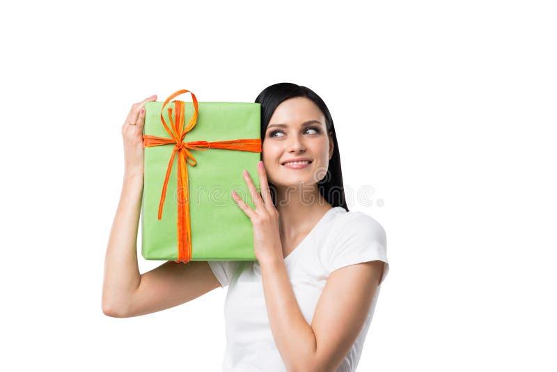 Eine Brunettefrau hält eine grüne Geschenkbox stockfotos