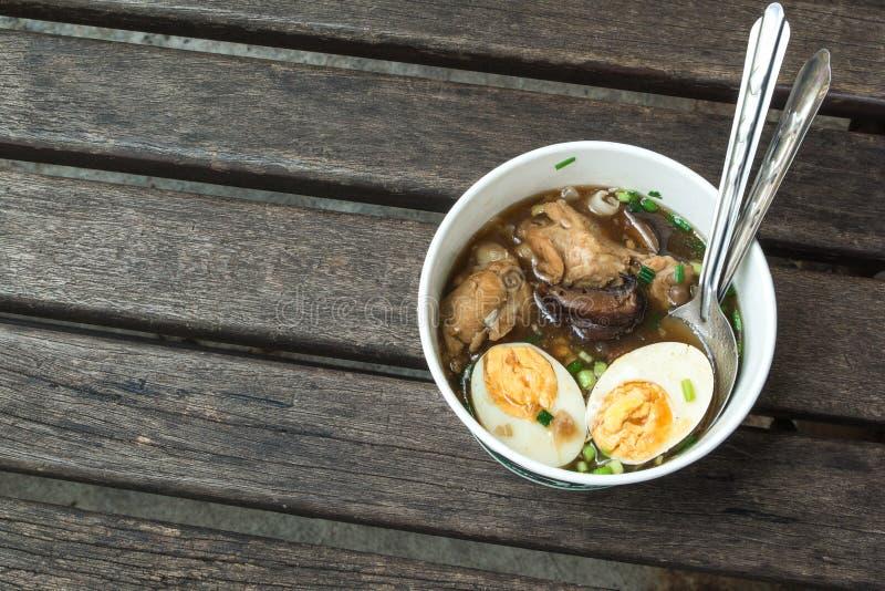 Eine chinesische Rollennudelsuppe mit gekochtem Ei auf der hölzernen Tabelle stockfotos