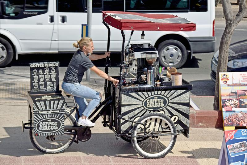 Eine Dame auf einem drei fahrbaren Fahrrad, das Getränke verkauft stockfotografie