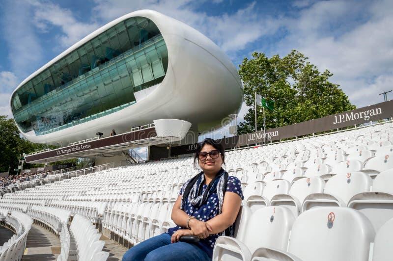 Eine Dame, die auf dem leeren Pavillon Cricketplatzes Lords mit der Medienmitte herein sitzt stockbilder