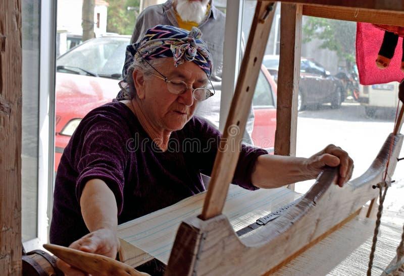 Eine Dame, die an einem Webstuhl arbeitet stockbild