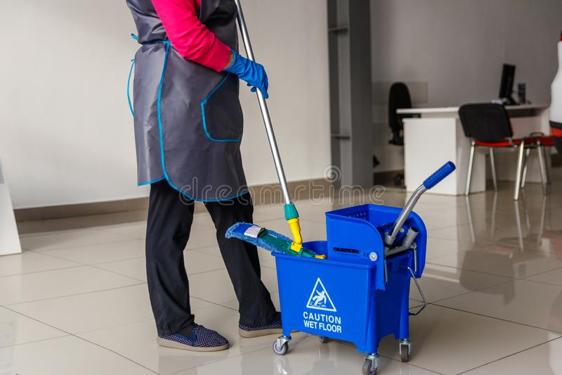eine Dame mit einem Eimer und einem MOPP, Reinigungsfirma stockfoto