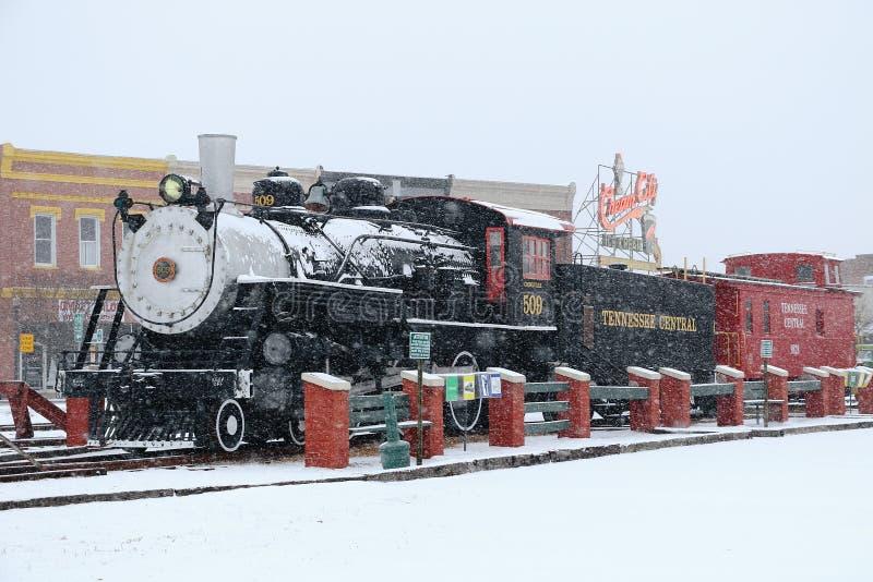 Eine Dampflokomotive sitzt in der Schnee bedeckten Kleinstadt stockbild