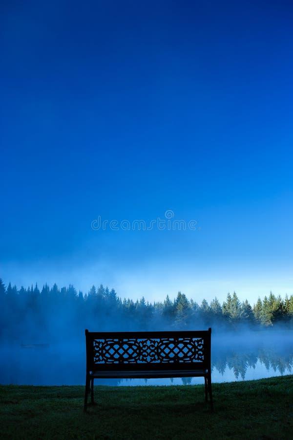 Eine dekorative Bank vor einem nebeligen Teich, Stowe Vermont, USA stockbilder