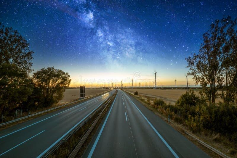 Eine deutsche Landstraße während Nacht mit Windkraftanlagen und Milchstraße stockfotografie