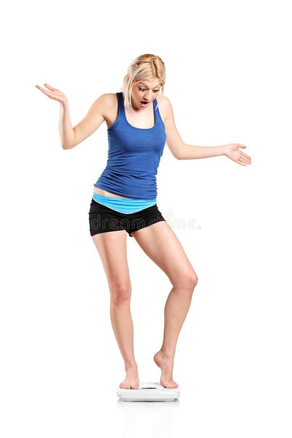 Eine disapointed junge Frau auf einer Gewichtskala lizenzfreies stockbild