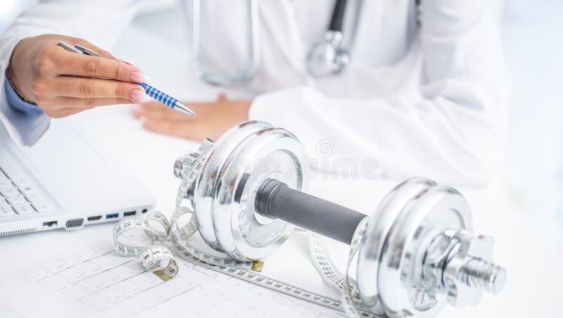 Eine Doktorfrau in den Operationen schreibt Sportbewegung und -Gewichtsverlust unter Verwendung der Dummköpfe und eines messenden stockfotos