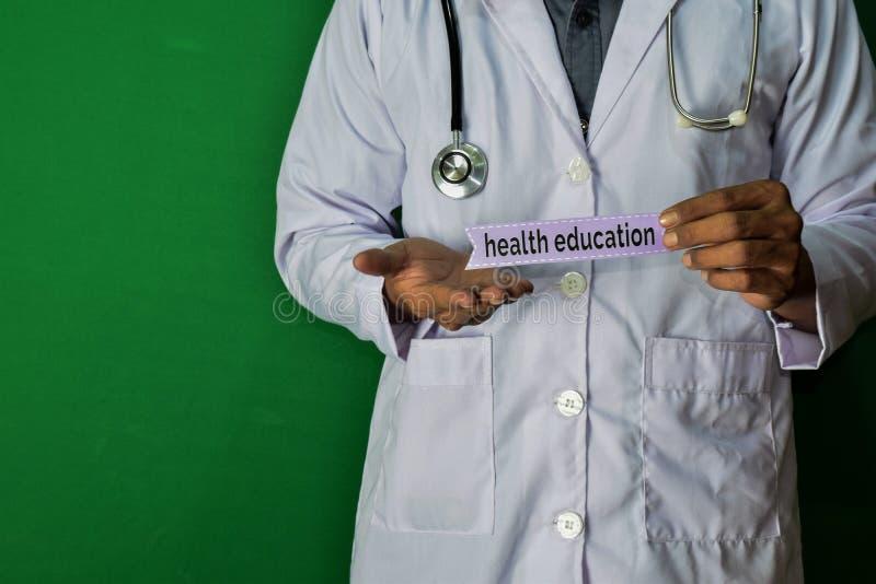 Eine Doktorstellung, halten den Gesundheitserziehungspapiertext auf grünem Hintergrund Medizinisches und Gesundheitswesenkonzept stockbilder