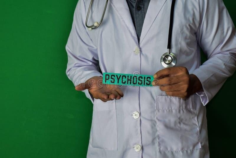 Eine Doktorstellung, halten den Psychosenpapiertext auf grünem Hintergrund Medizinisches und Gesundheitswesenkonzept lizenzfreies stockfoto
