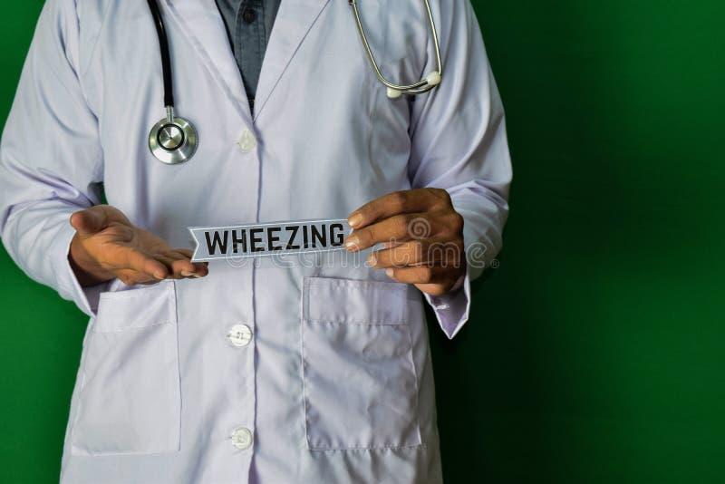 Eine Doktorstellung, halten den schnaufenden Papiertext auf grünem Hintergrund Medizinisches und Gesundheitswesenkonzept stockbild