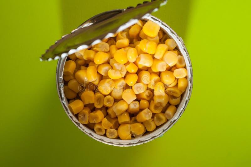 Eine Dose Mais in Büchsen konserviert auf einem schwarzen Hintergrund, öffnete sich mit einem speziellen Öffnermesser lizenzfreie stockfotos