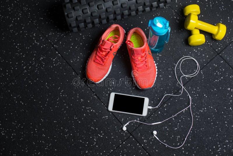 Eine Draufsicht des sportiven Zubehörs für Turnhallentraining Tragen Sie Schuhe, Stummglocken, Flasche und Telefon auf einem schw stockbild