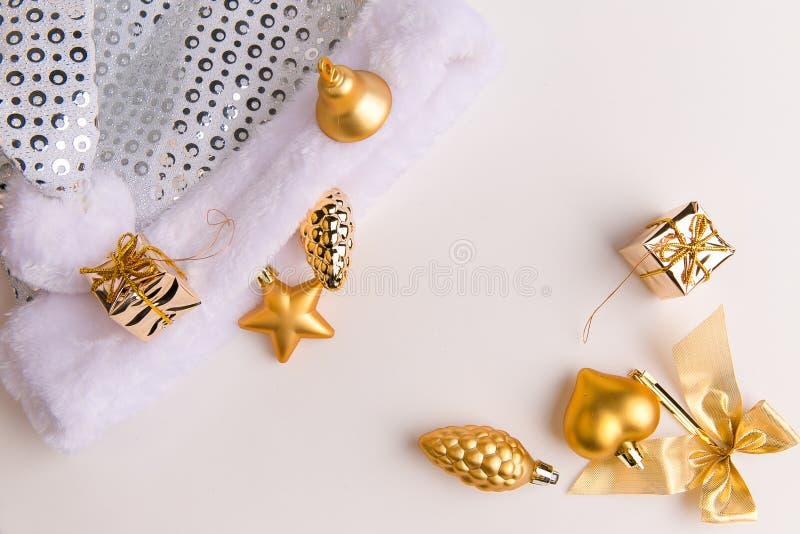 Eine Draufsicht von goldenen Farbeweihnachtsverzierungen und von Sankt-` weißer und silberner Pelzhut s auf einem weißen Hintergr lizenzfreies stockfoto