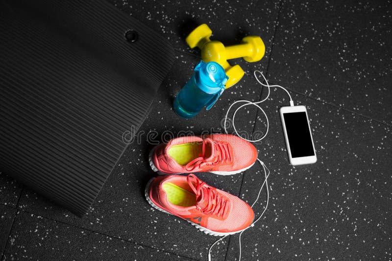 Eine Draufsicht von orange Sportschuhen, von gelben Stummglocken, von pilates Matte, von Portugiesischer Galeere und von Telefon  lizenzfreies stockfoto