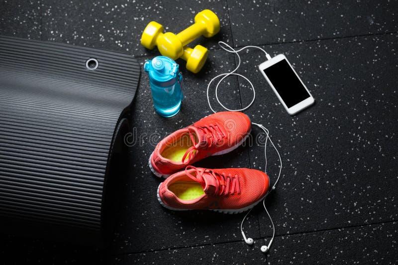 Eine Draufsicht von orange Sportschuhen, von gelben Stummglocken, von pilates Matte, von Portugiesischer Galeere und von Telefon  stockbilder
