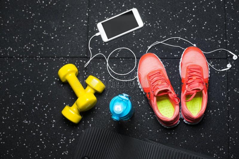Eine Draufsicht von orange Sportschuhen, von gelben Stummglocken, von pilates Matte, von Portugiesischer Galeere und von Telefon  lizenzfreies stockbild