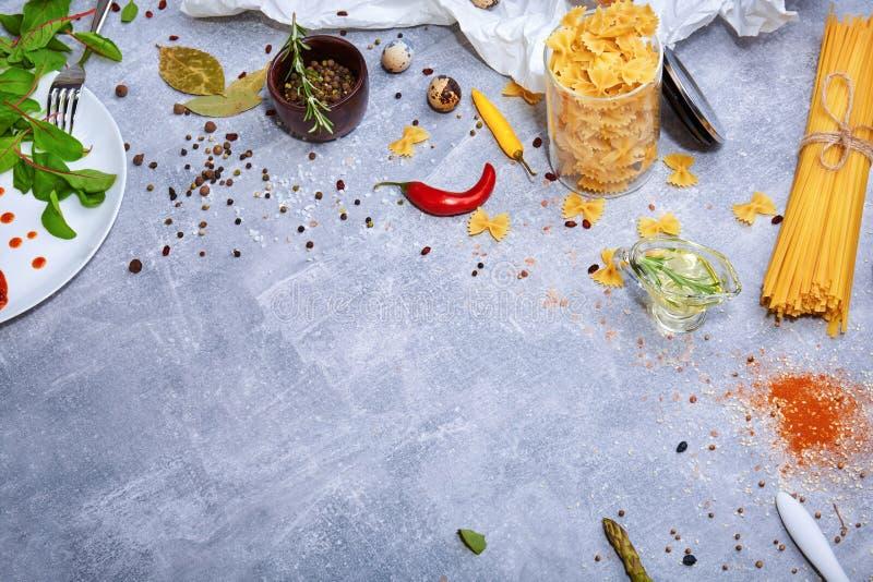 Eine Draufsicht von Teigwaren auf einem grauen Steinhintergrund Nudeln, fusilli und glühende Paprikapfeffer Geschmackvolle italie stockfotografie