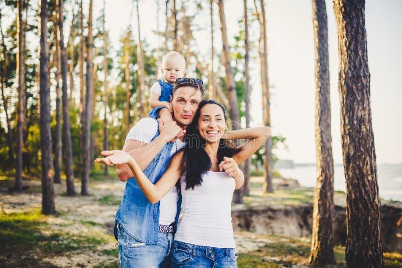 Eine dreiköpfige Familie, junge schöne Eltern, die mit ihrer Tochter sitzt auf den Schultern des Papstes ein Jahr nach Geburt I s stockfotos