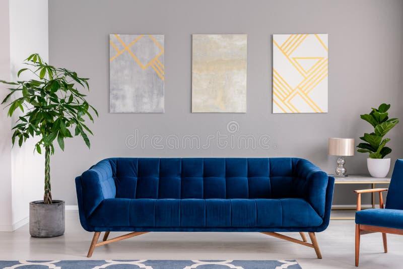 Eine dunkelblaue Samtcouch vor einer grauen Wand mit grafischen Malereien in einem modernen Wohnzimmerinnenraum Reales Foto stockfoto