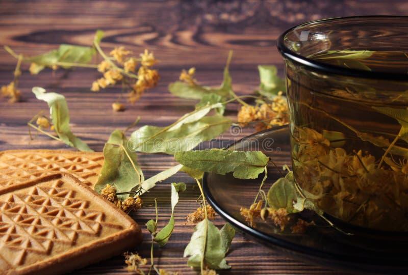 Eine dunkle Schale Gesundheitstee, Lindeblumen und Quadrate von Plätzchen sind auf dem Tisch lizenzfreie stockfotos