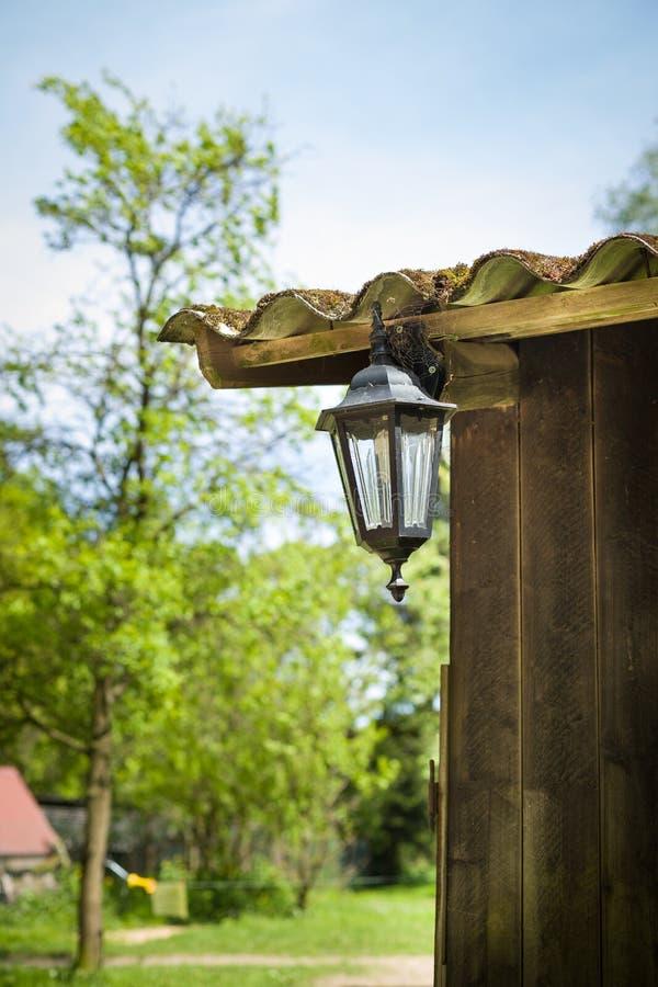 Eine Ecke eines alten Holzhauses mit Retro- Laterne auf dem Dach Sommer in der Landschaft lizenzfreies stockfoto