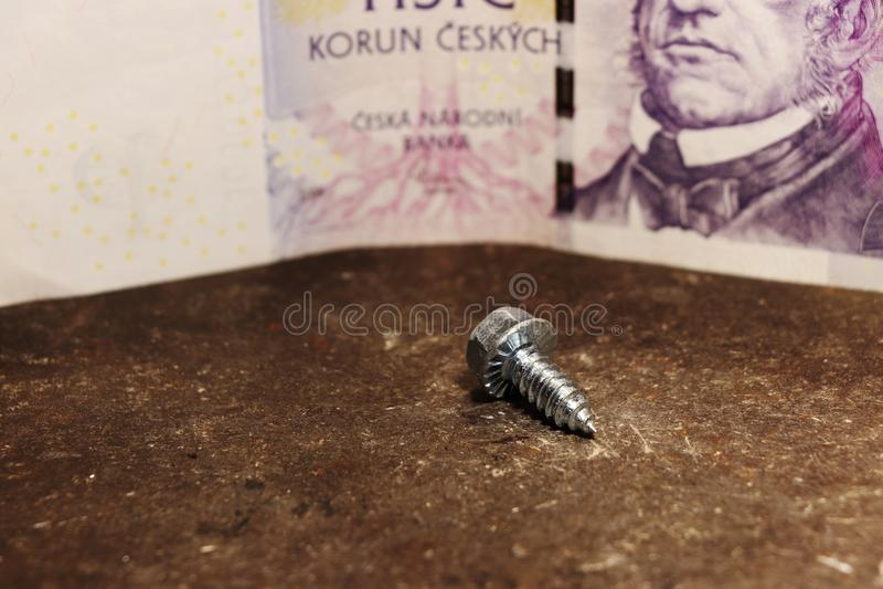 Eine ein kleine Metallschraube mit tausend tschechischen Kronen stockbilder