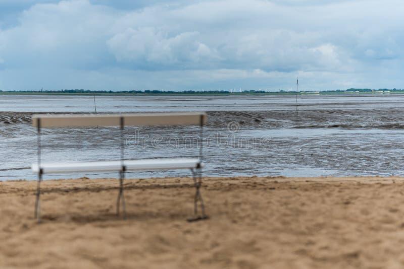 Eine einsame Bank auf einem Strand am ebbe stockfoto