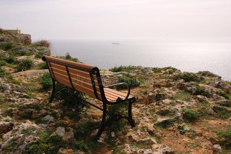 Eine einsame Bank auf einer felsigen Ozeanküste stockfoto