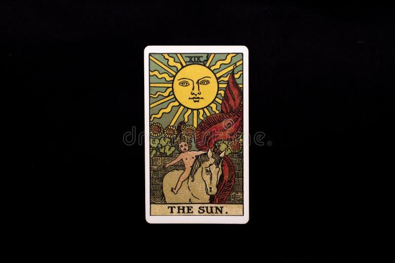 Eine einzelne bedeutende Arcanatarockkarte lokalisiert auf schwarzem Hintergrund Die Sonne lizenzfreie stockfotografie