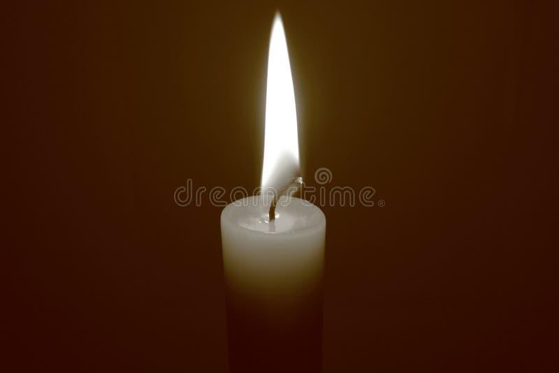 Eine einzelne brennende Kerze auf dunklem Hintergrund Gro?er Raum f?r Kopie stockfotografie