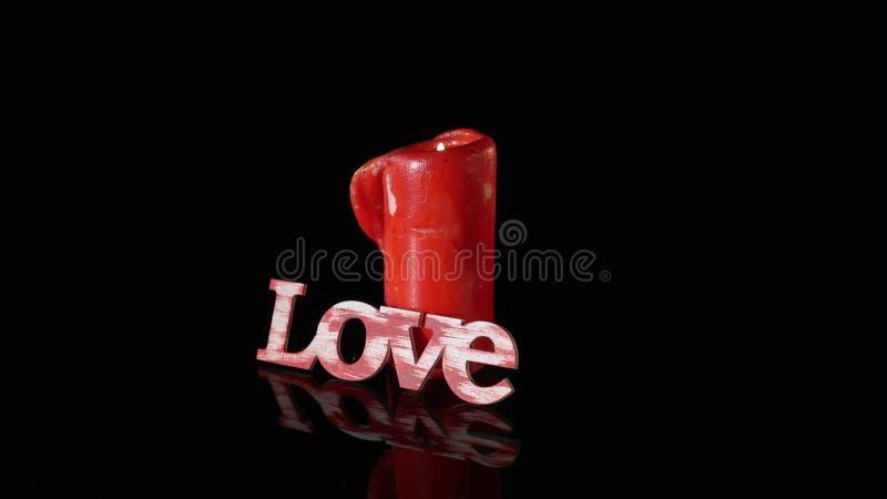 Eine einzelne brennende rote Kerze drehen sich vor schwarzem Hintergrund lizenzfreies stockbild