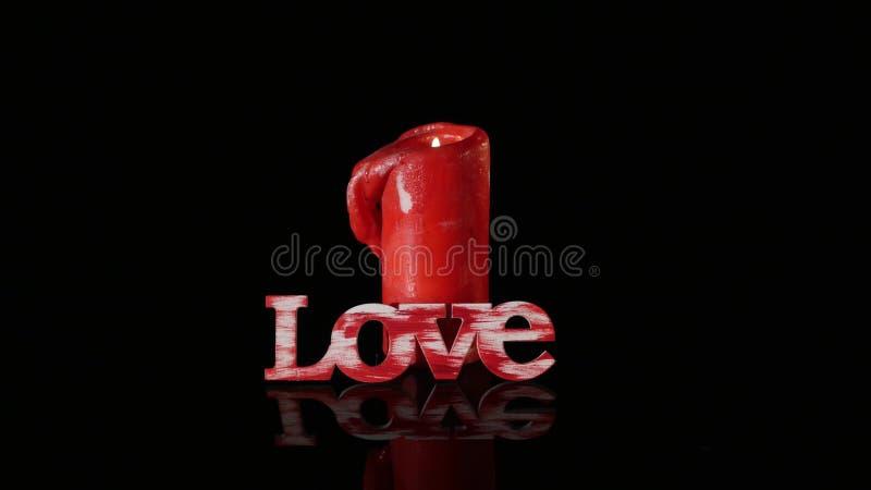 Eine einzelne brennende rote Kerze drehen sich vor schwarzem Hintergrund stockfoto