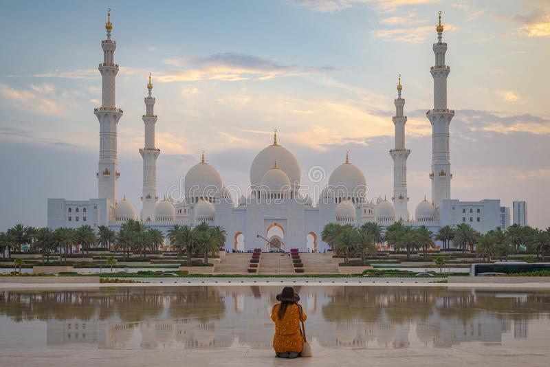 Eine einzelne Damenfrau, die eine axiale Ansicht der großen Moschee von Abu Dhabi bei Sonnenuntergang betrachtet stockbilder