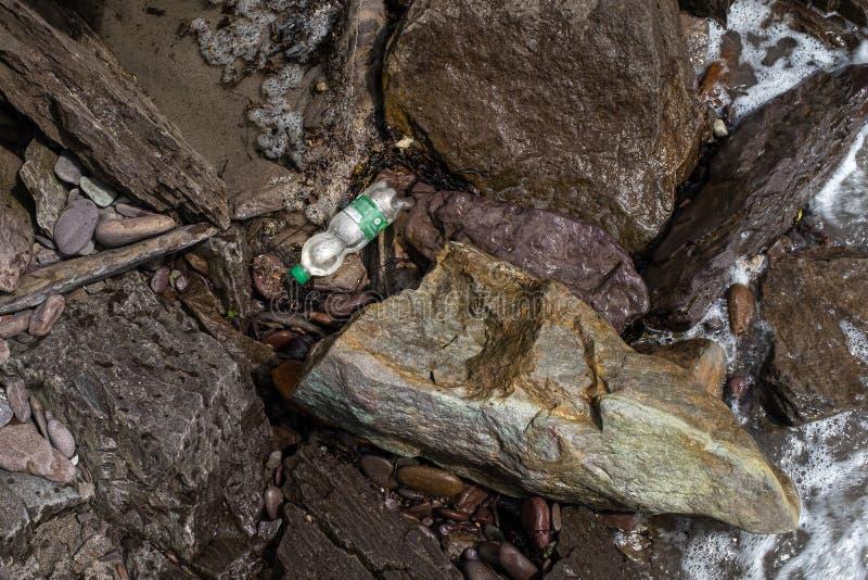 Eine einzelne Plastikflasche wird oben zwischen Felsen auf der K?stenlinie von Irland gewaschen stockfoto