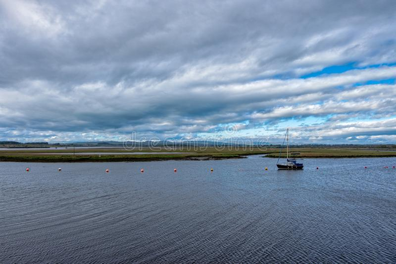 Eine einzelne Yacht legte heraus im Irvine-Hafen an einem windigen Tag in Schottland an stockbilder