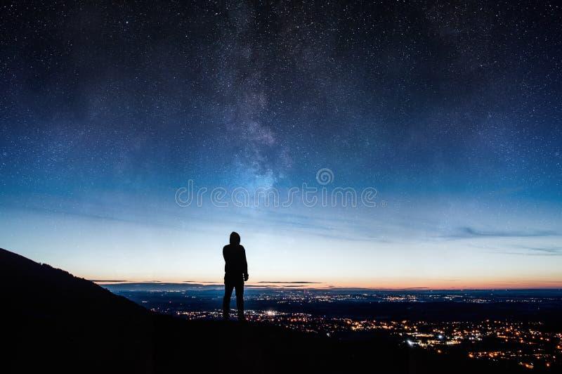 Eine einzige silhouettierte mit Kapuze Zahl Stellung auf einem Hügel, der unten auf Stadtlichtern Nacht mit einer Galaxie und Ste stockfoto