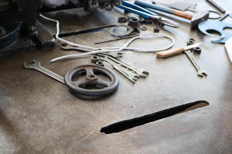 Eine Eisentabelle mit einem Metallverarbeitungswerkzeug, Schlüssel, Hämmer, Schraubenzieher, Quetschwalzen, Messer, Ventile in de stockfotografie