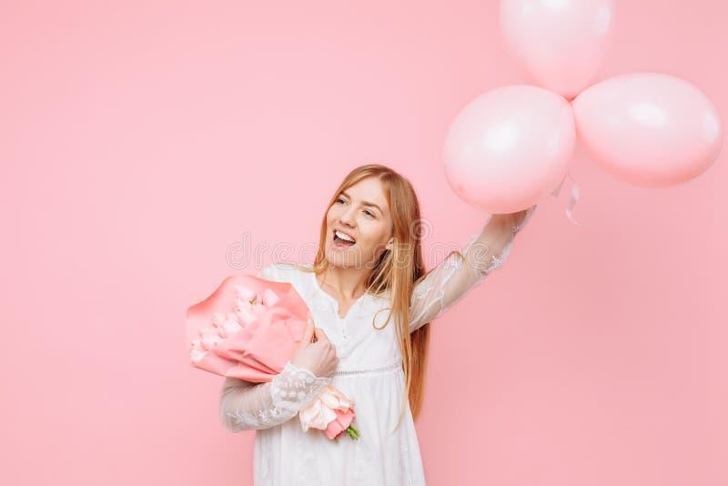 Eine enthusiastische junge Frau, in einem weißen Kleid, stehend mit rosa Tulpen und Ballonen, auf einem rosa Hintergrund 8. März  stockfoto